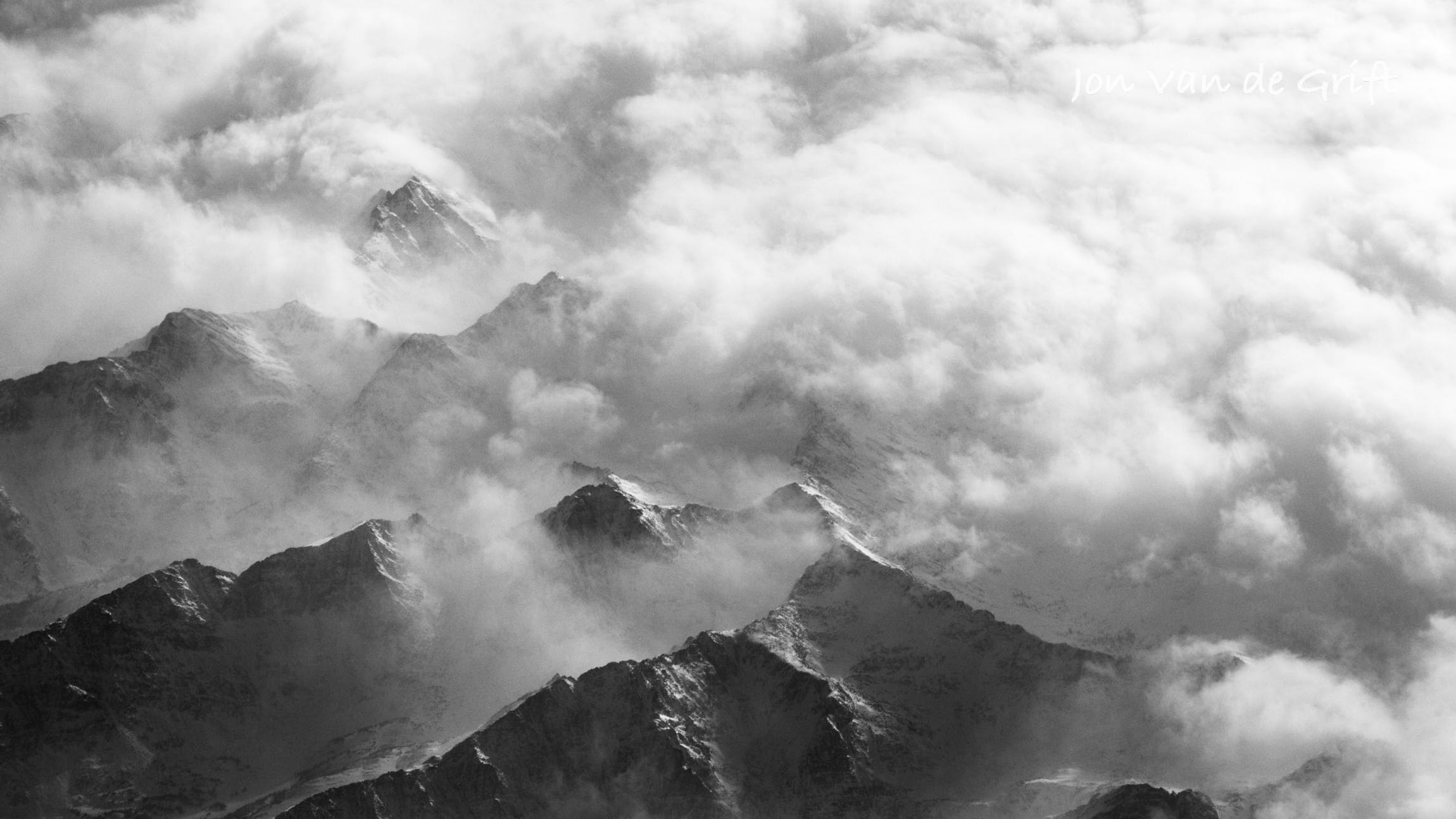 Black and white aerial photograph of clouds over a snow covered mountain range in winter
