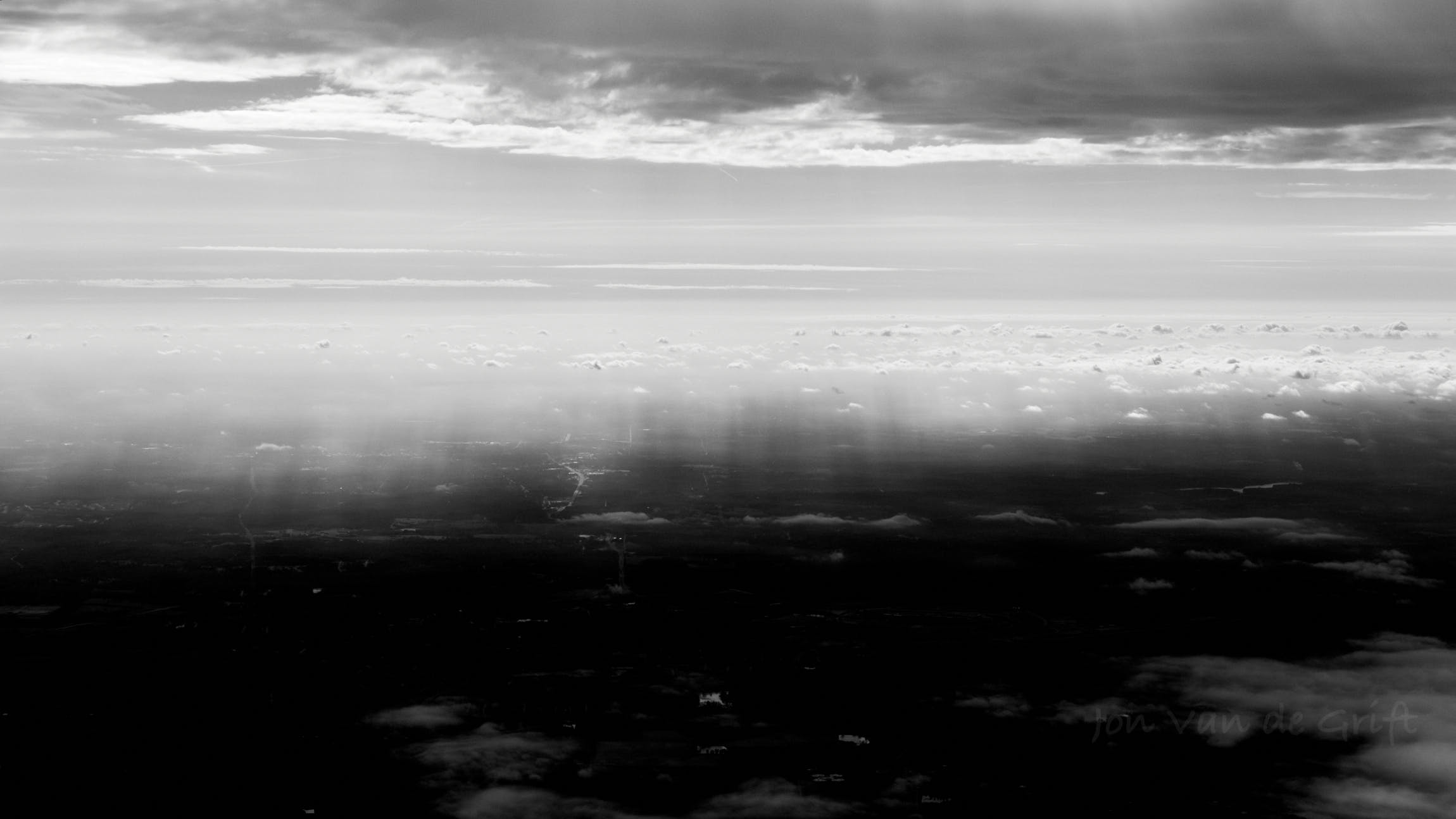 Black and white aerial photograph captured flying between cloud layers.