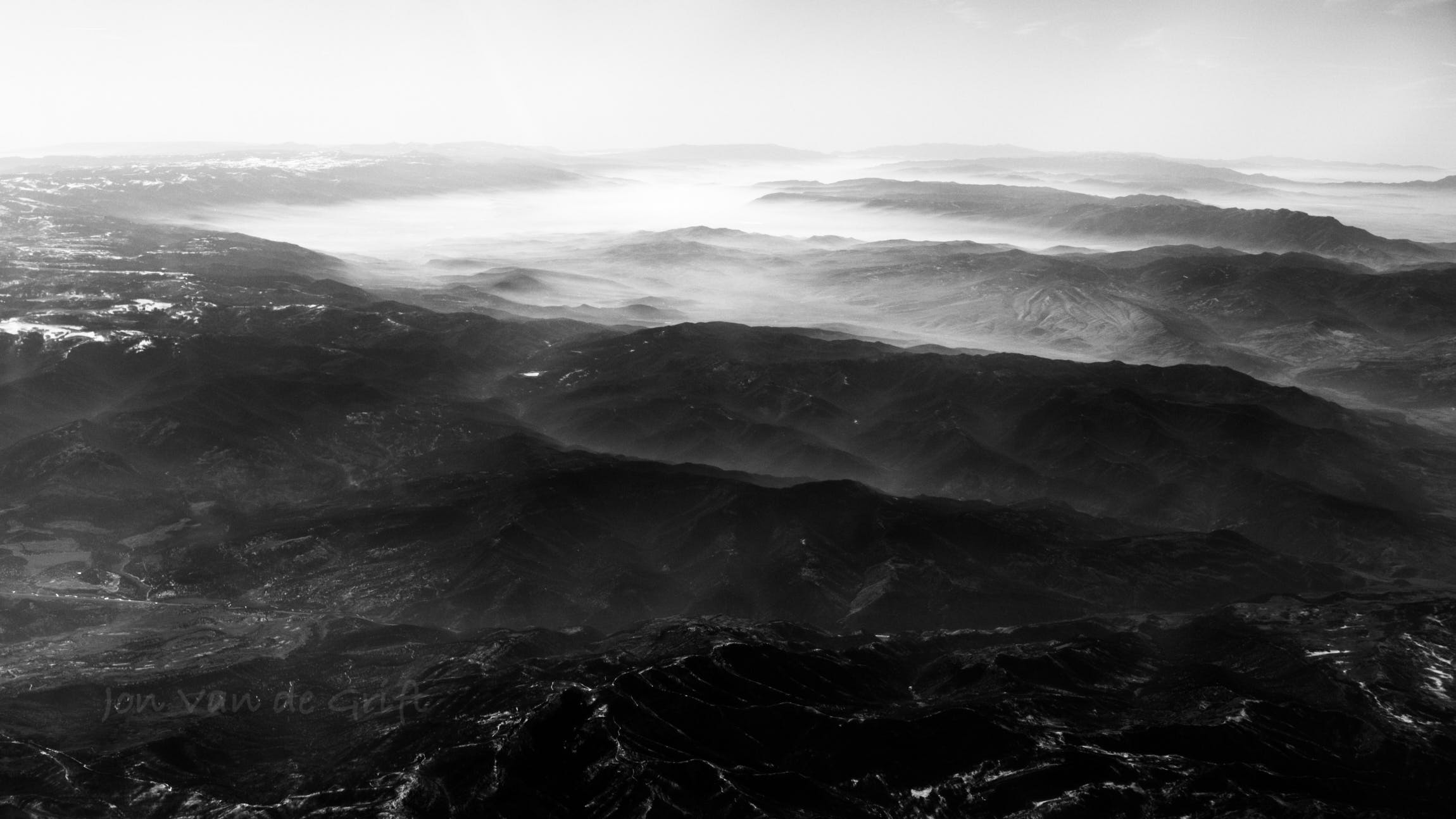 Black and white aerial photograph of haze in mountain valleys.