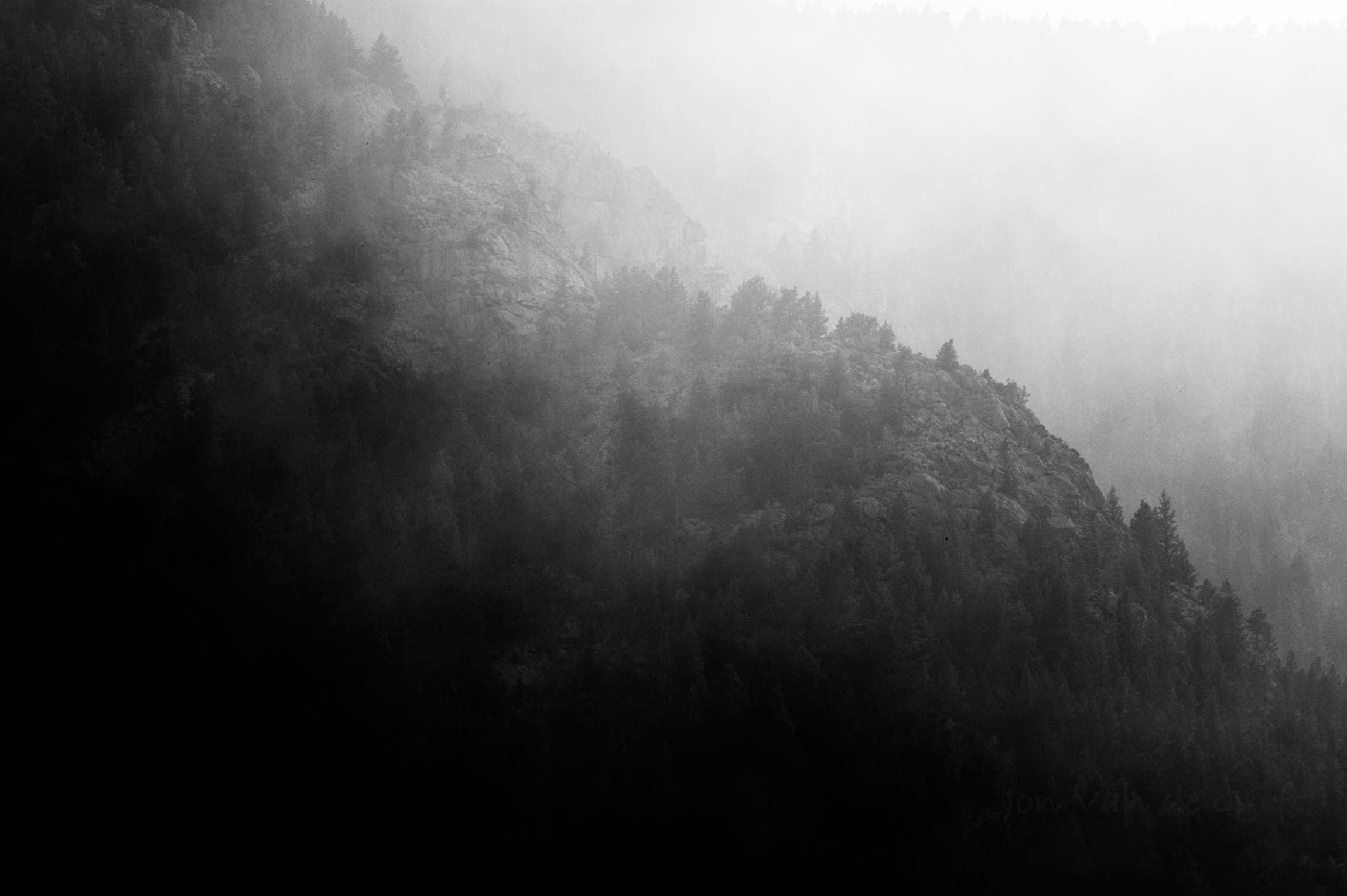 Black and white photograph of smoke from a fire on a forested mountain