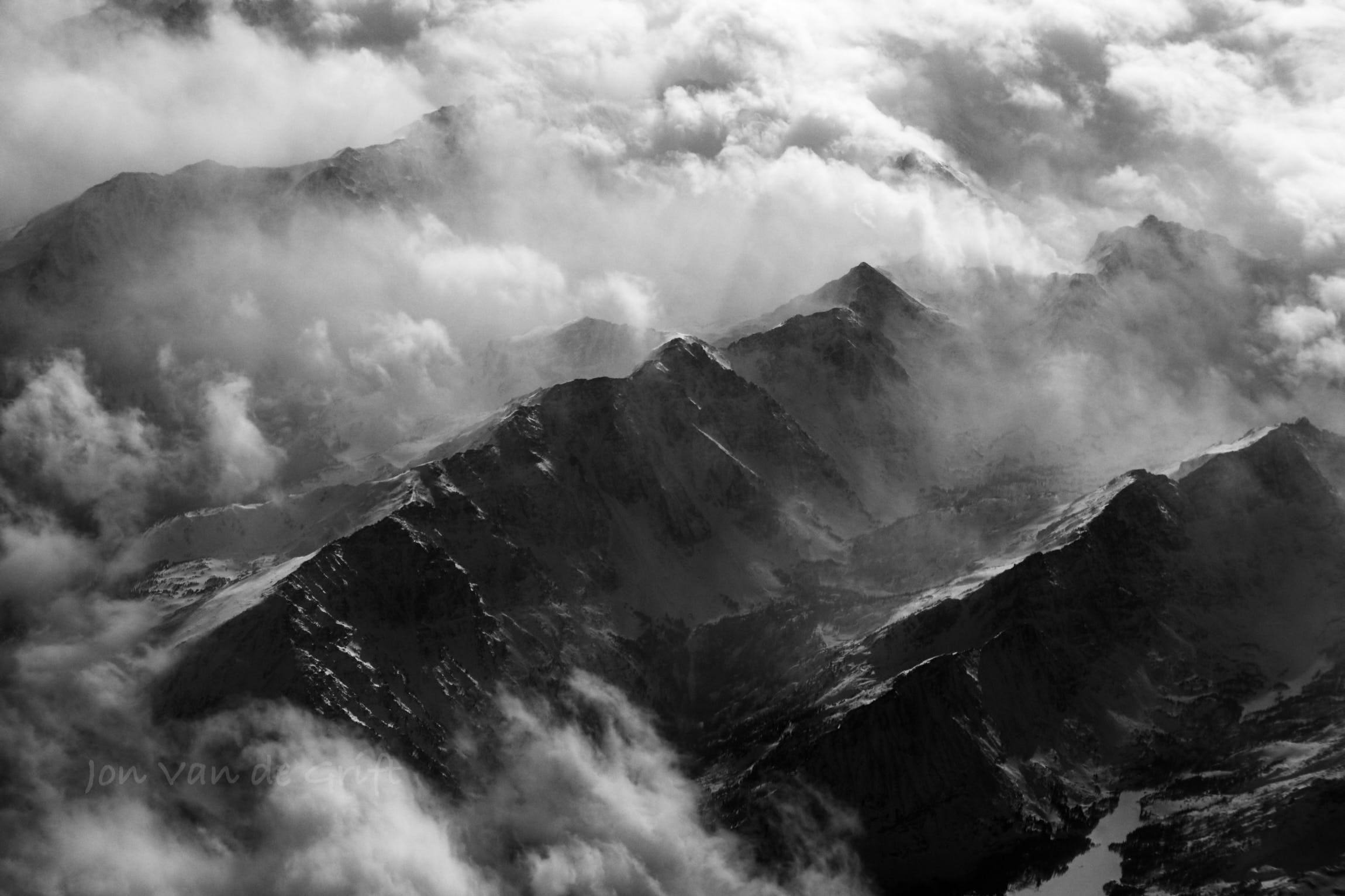Black and white aerial photograph of clouds surrounding mountains.
