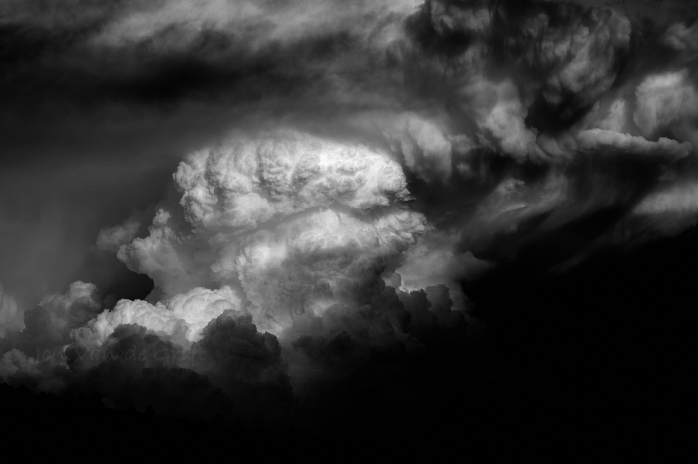 Black and white aerial photograph of thunderstorm clouds at sunset