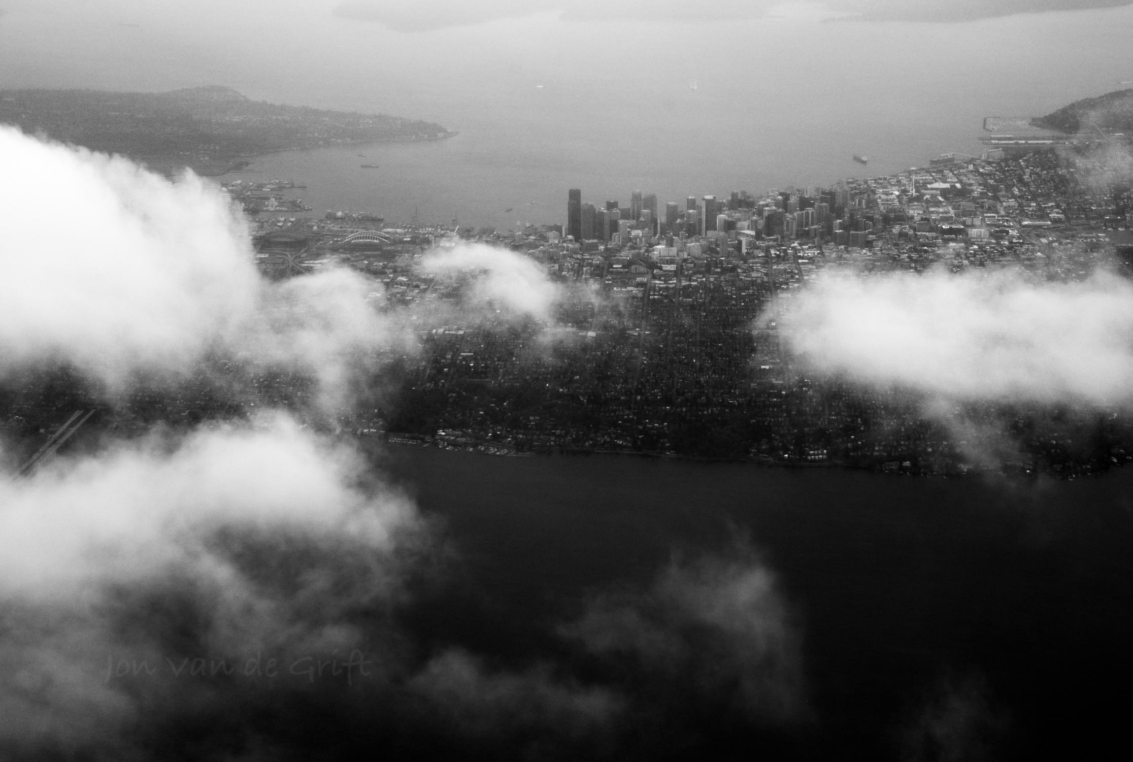 Black and white aerial photograph of the city of Seattle surrounded by clouds.