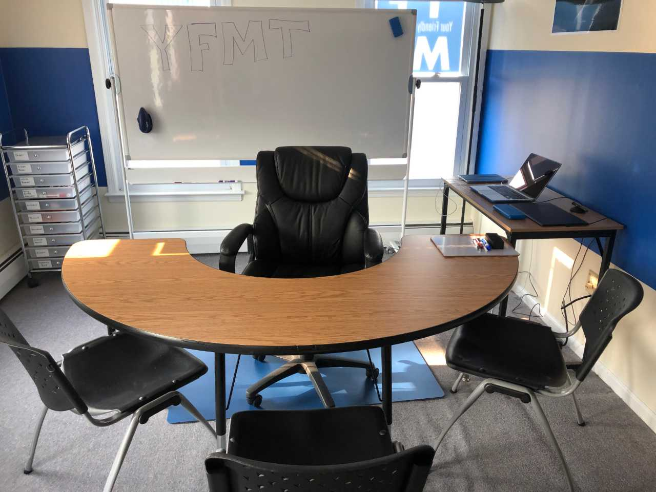 Half moon desk set up for group math tutoring with large whiteboard and other technologies