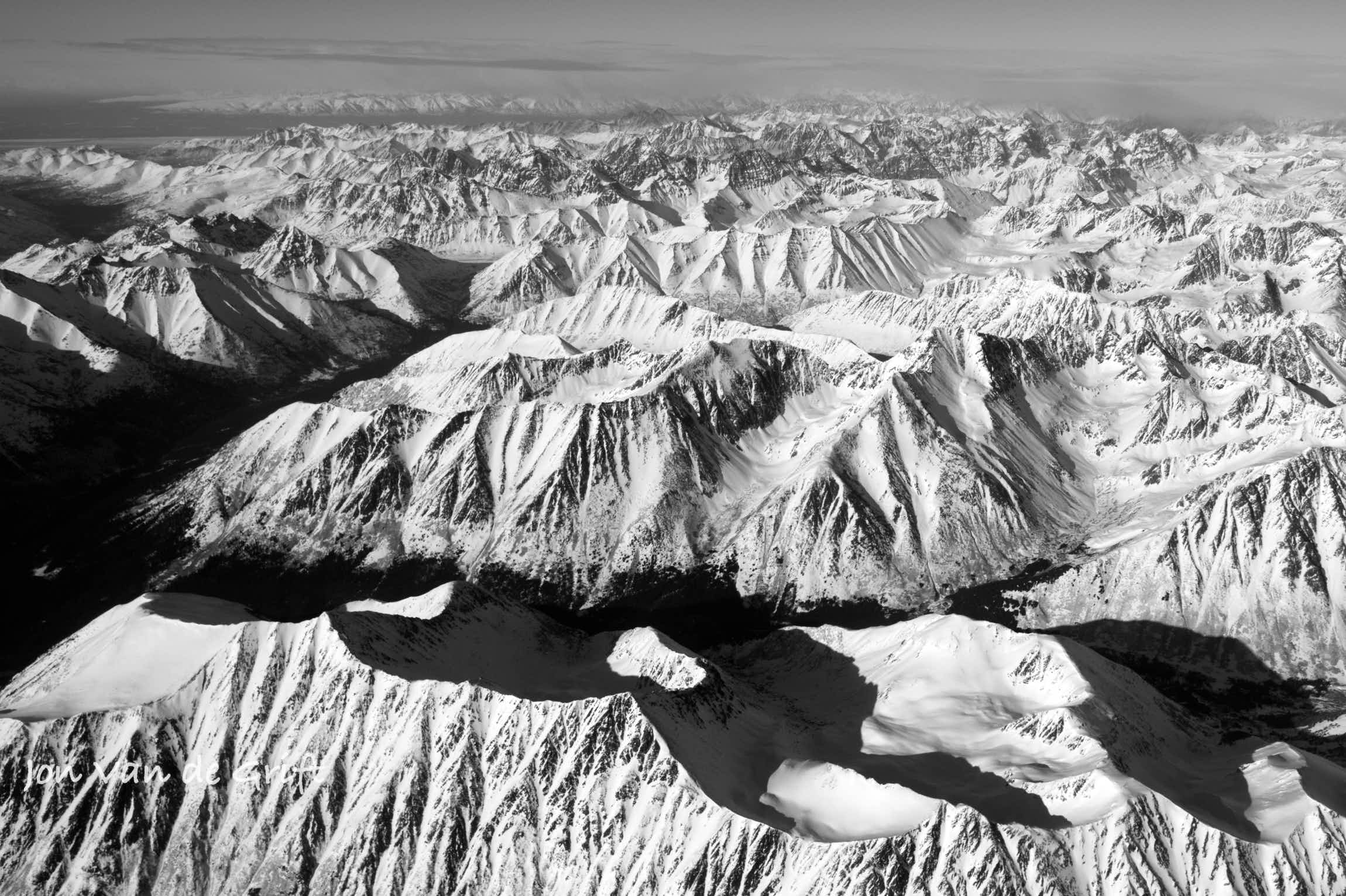 Black and white aerial photograph of Arctic mountain ranges in winter.
