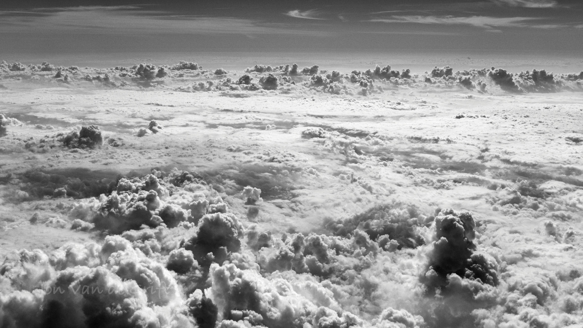Monochromatic aerial photograph flying above clouds.