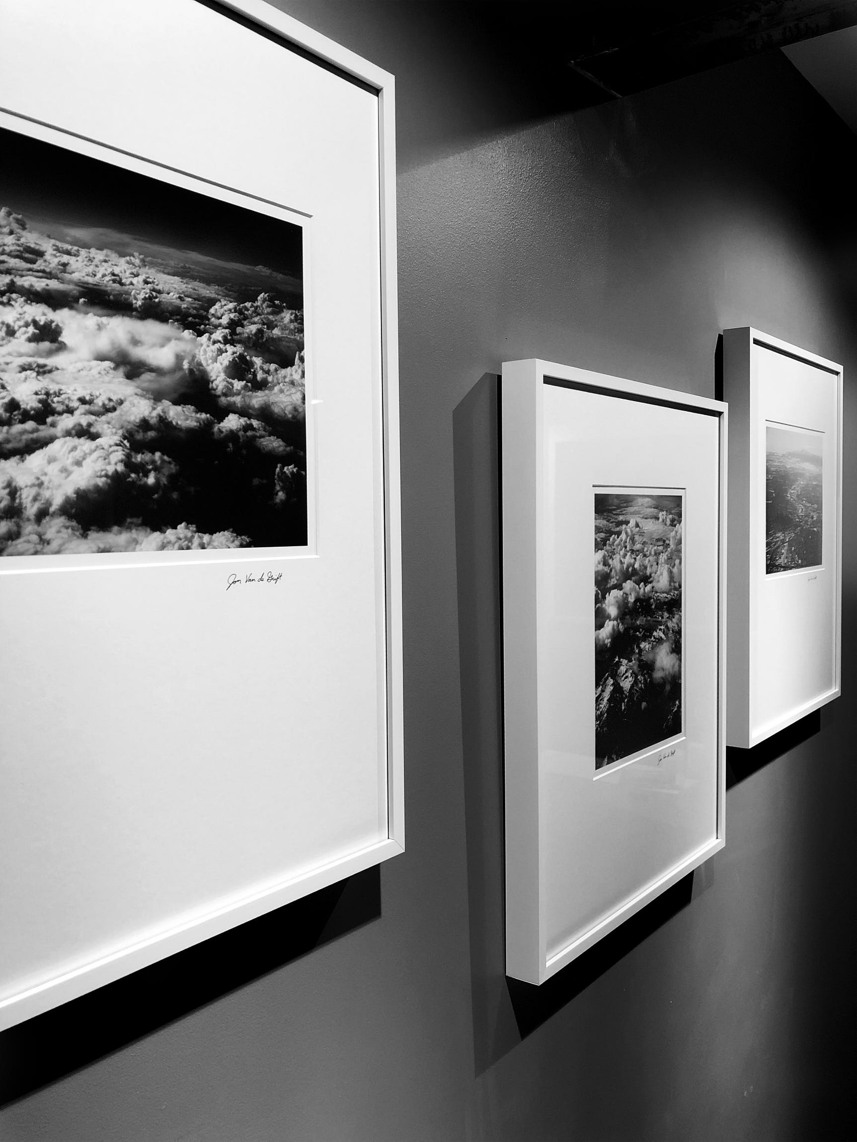 Photograph of framed black and white photos hanging on a wall