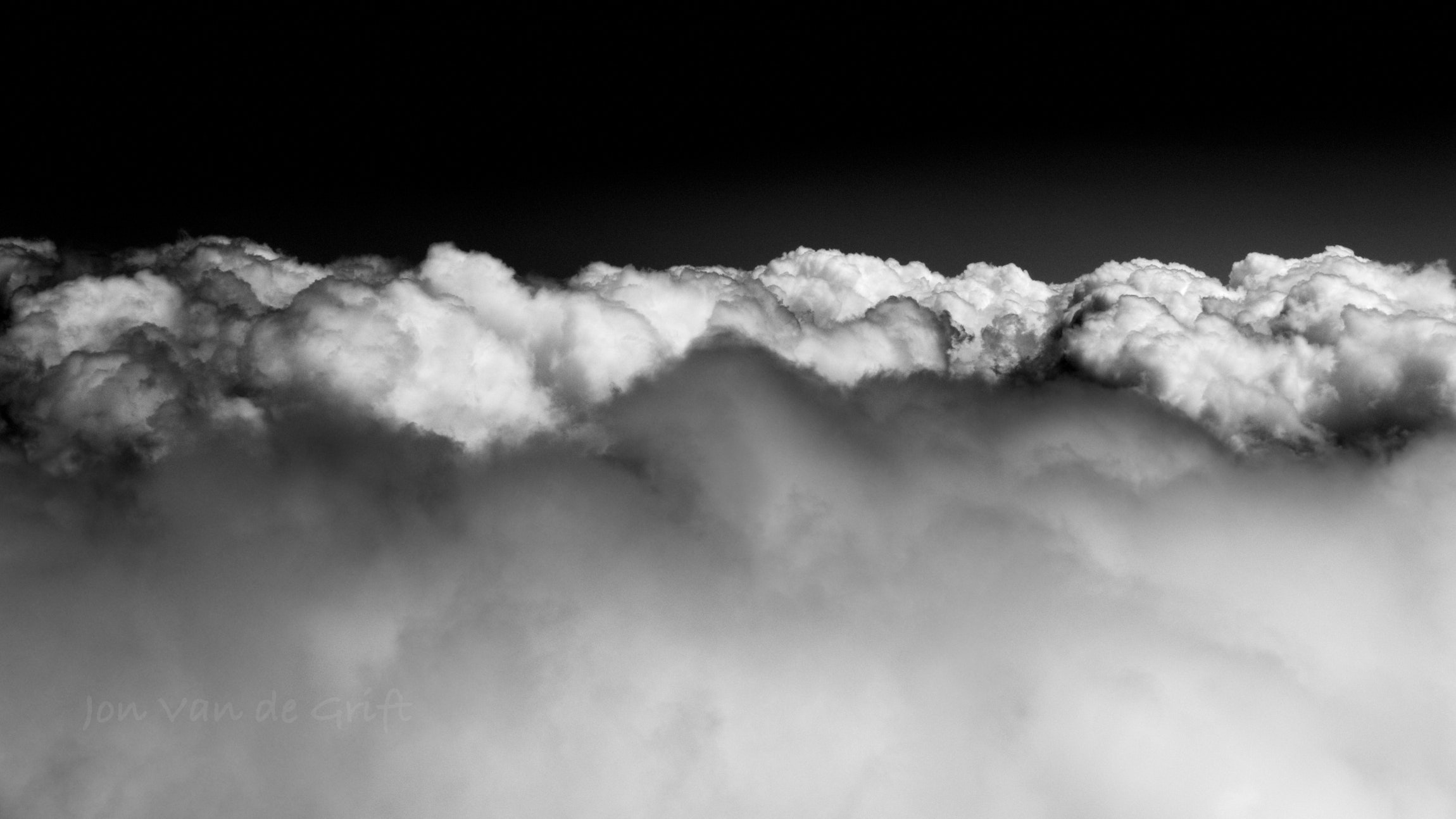 Black and white aerial photograph of sun reflecting off cumulus clouds.