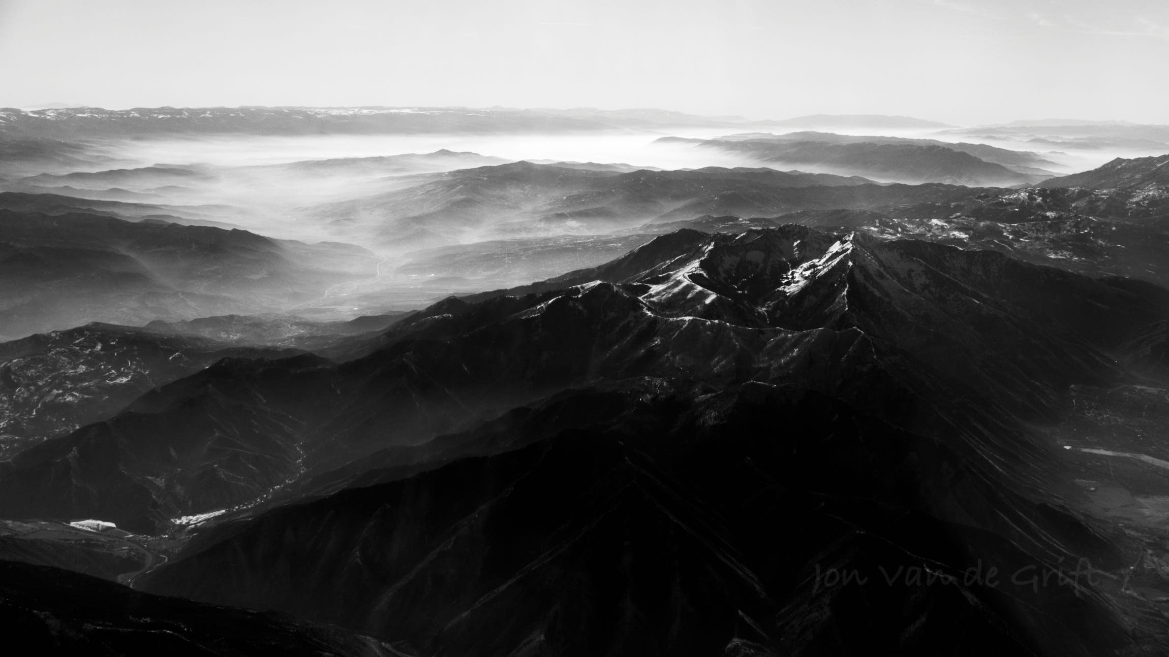 Black and white aerial photograph of mountain ranges with snow.