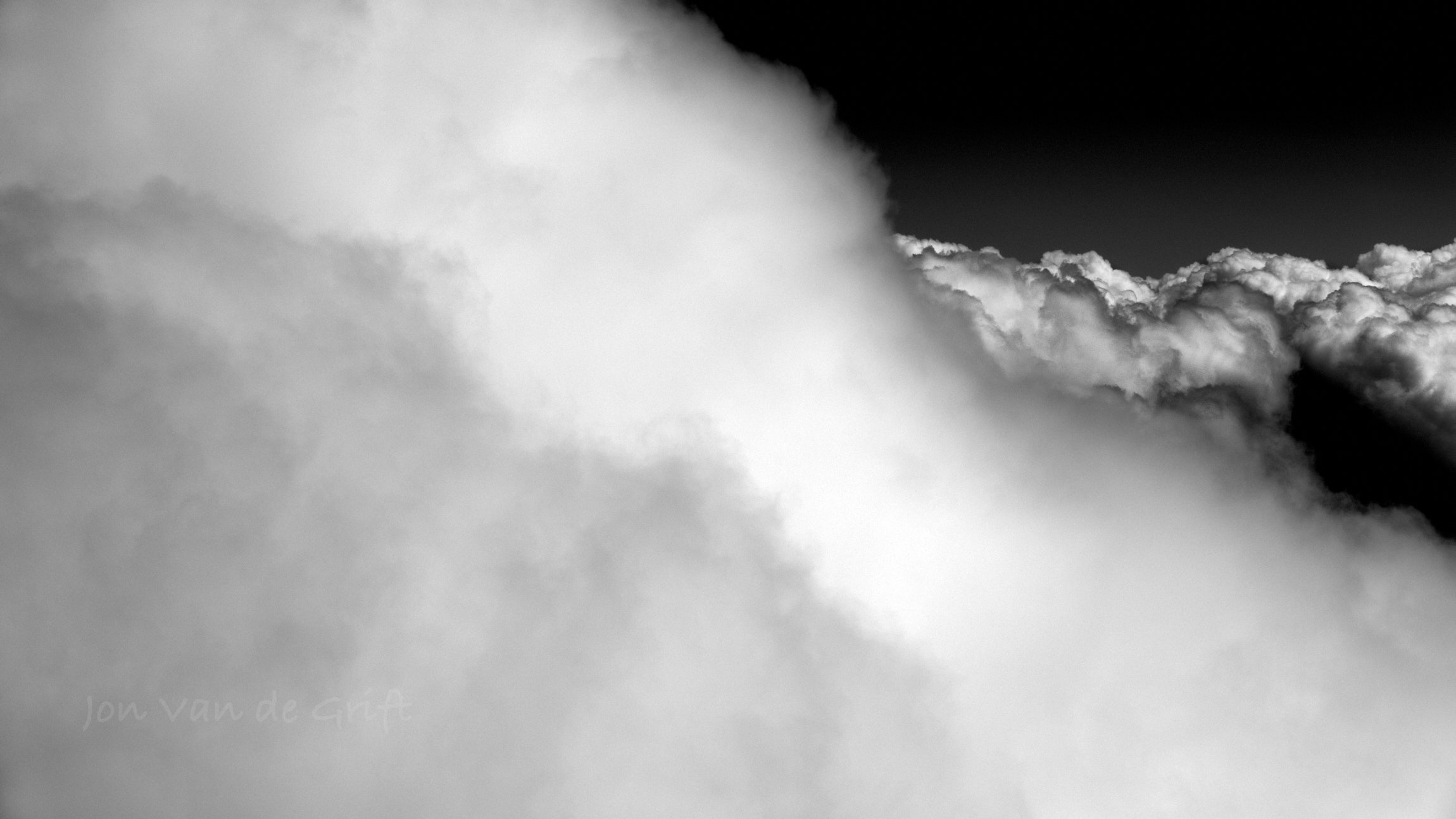 Monochromatic aerial photograph captured from within cumulus clouds.