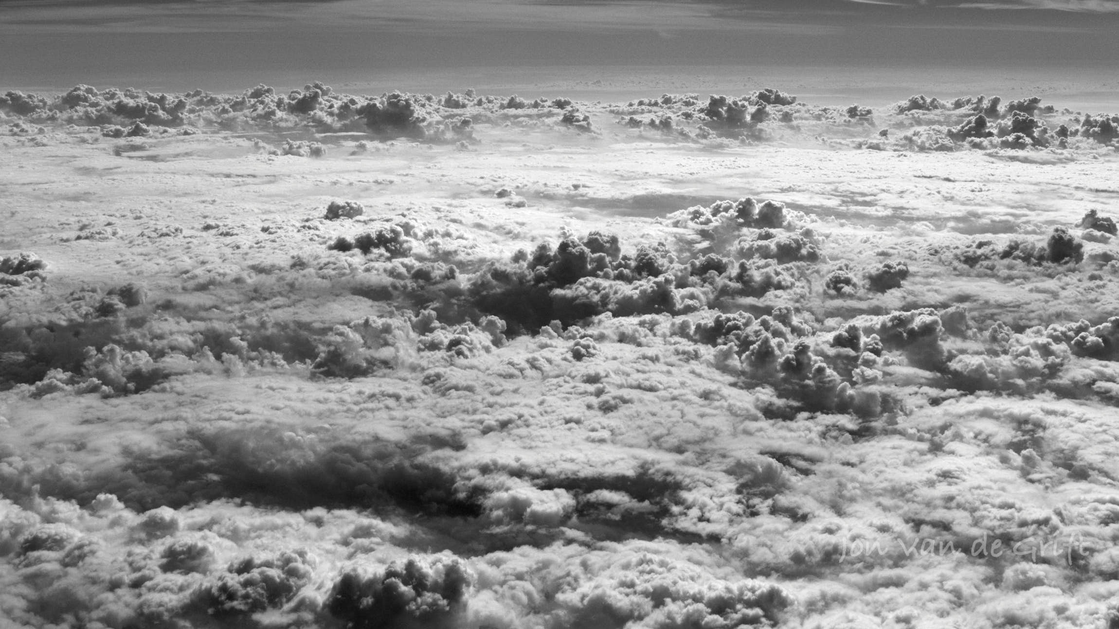 Monochrome aerial photograph of sun reflecting off cumulus cloud tops with a distant horizon.