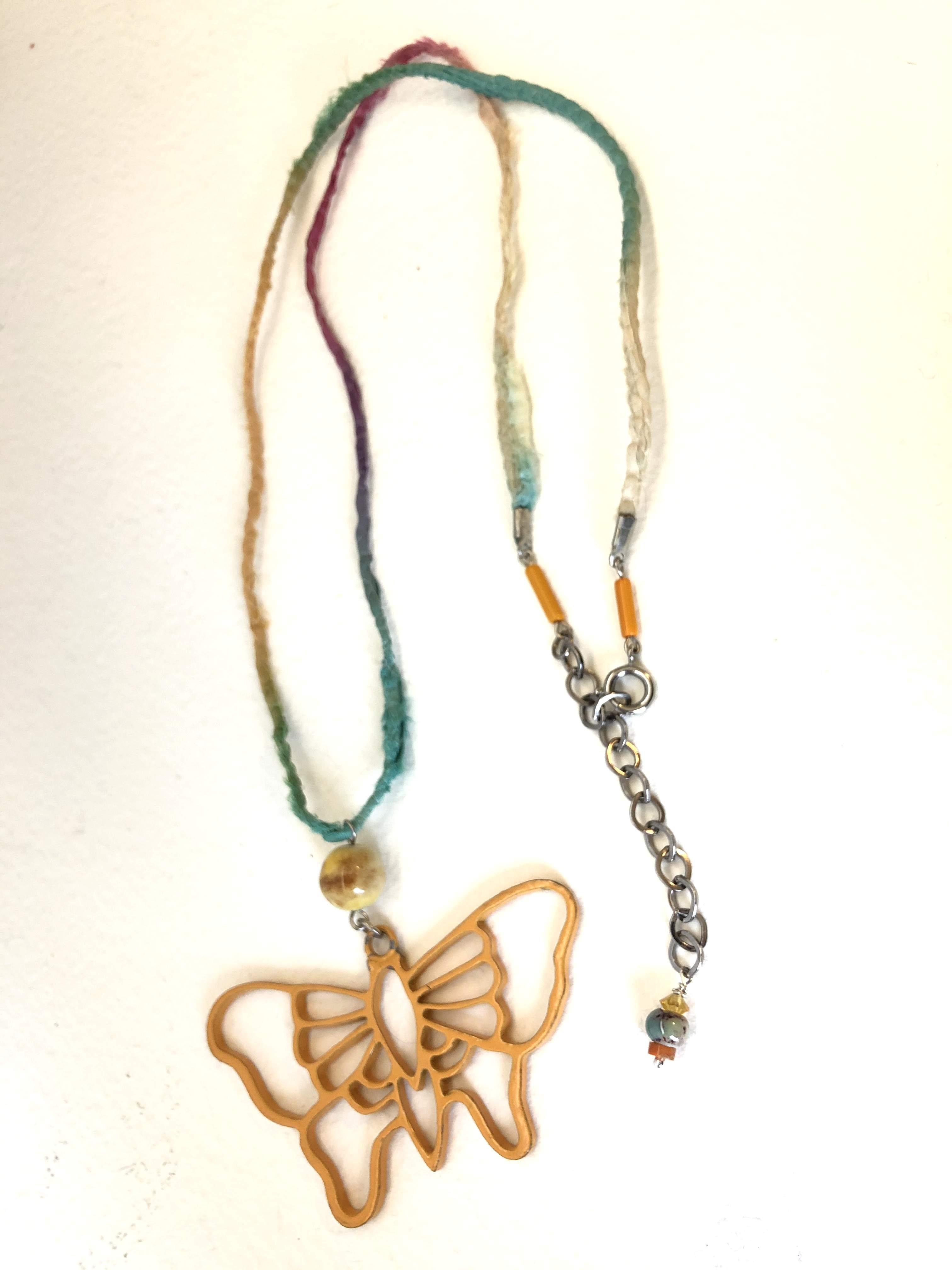 A rescued butterfly pendant, featured on a colorful sari cord with added porcelain beads, adjustable