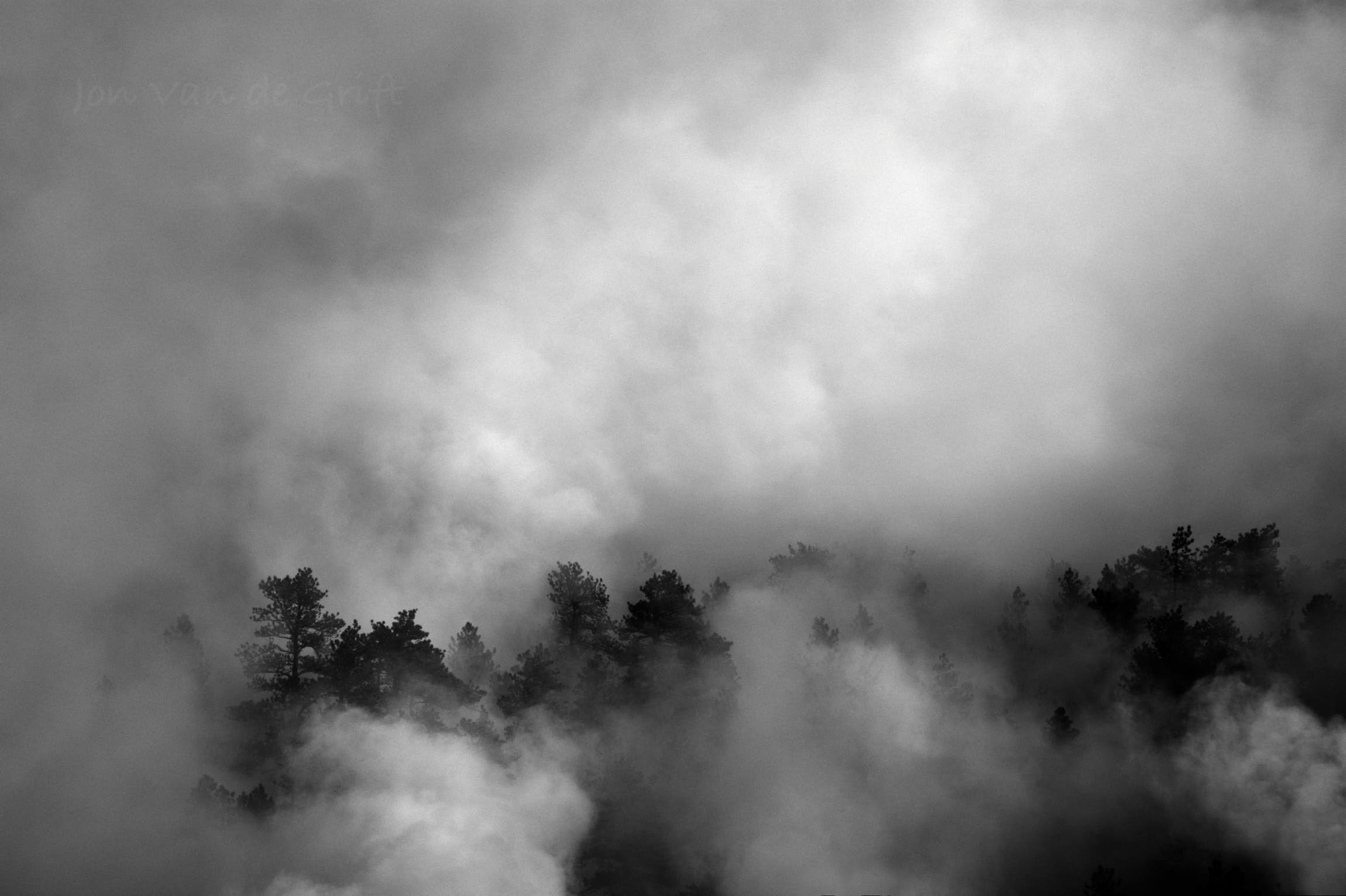 Black and white aerial photograph of a fire with smoke in a forest