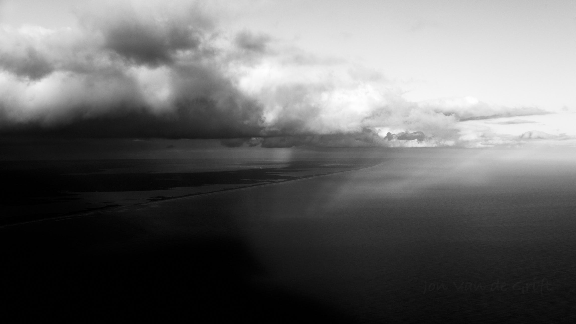 Monochrome aerial photograph of a storm over islands in the ocean.