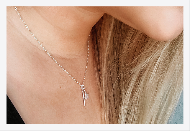 blond woman wearing crystal quartz bar necklace