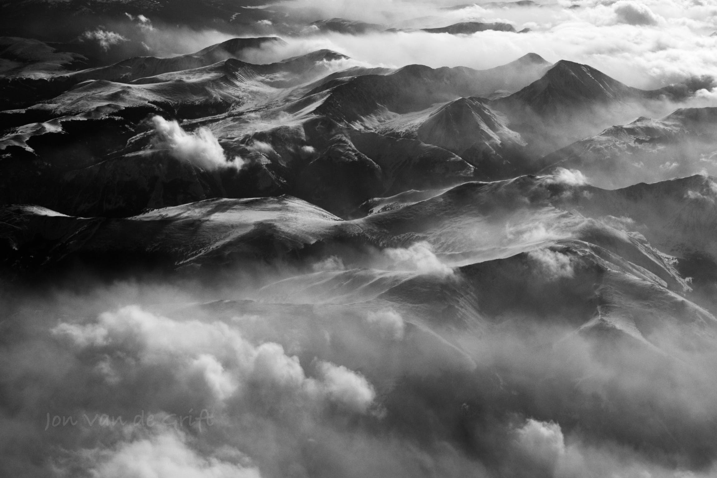 Black and white aerial photograph of clouds near sunset over a mountain range in winter, captured with a Leica camera.