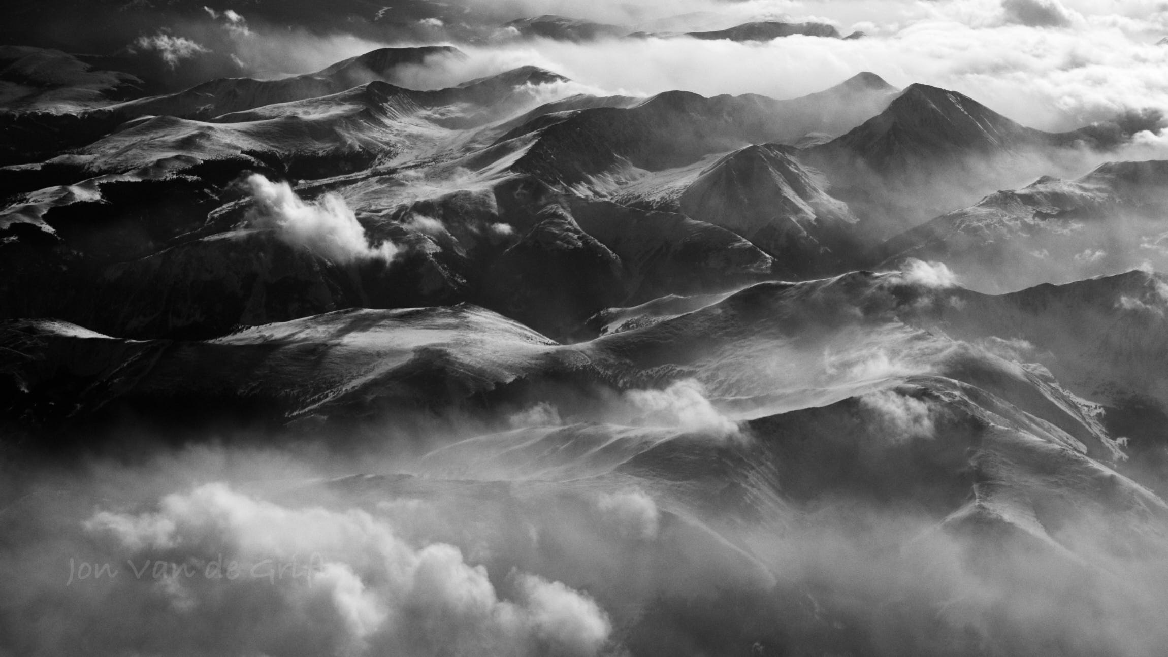 Black and white aerial photograph of shadow falling around a mountain range near sunset