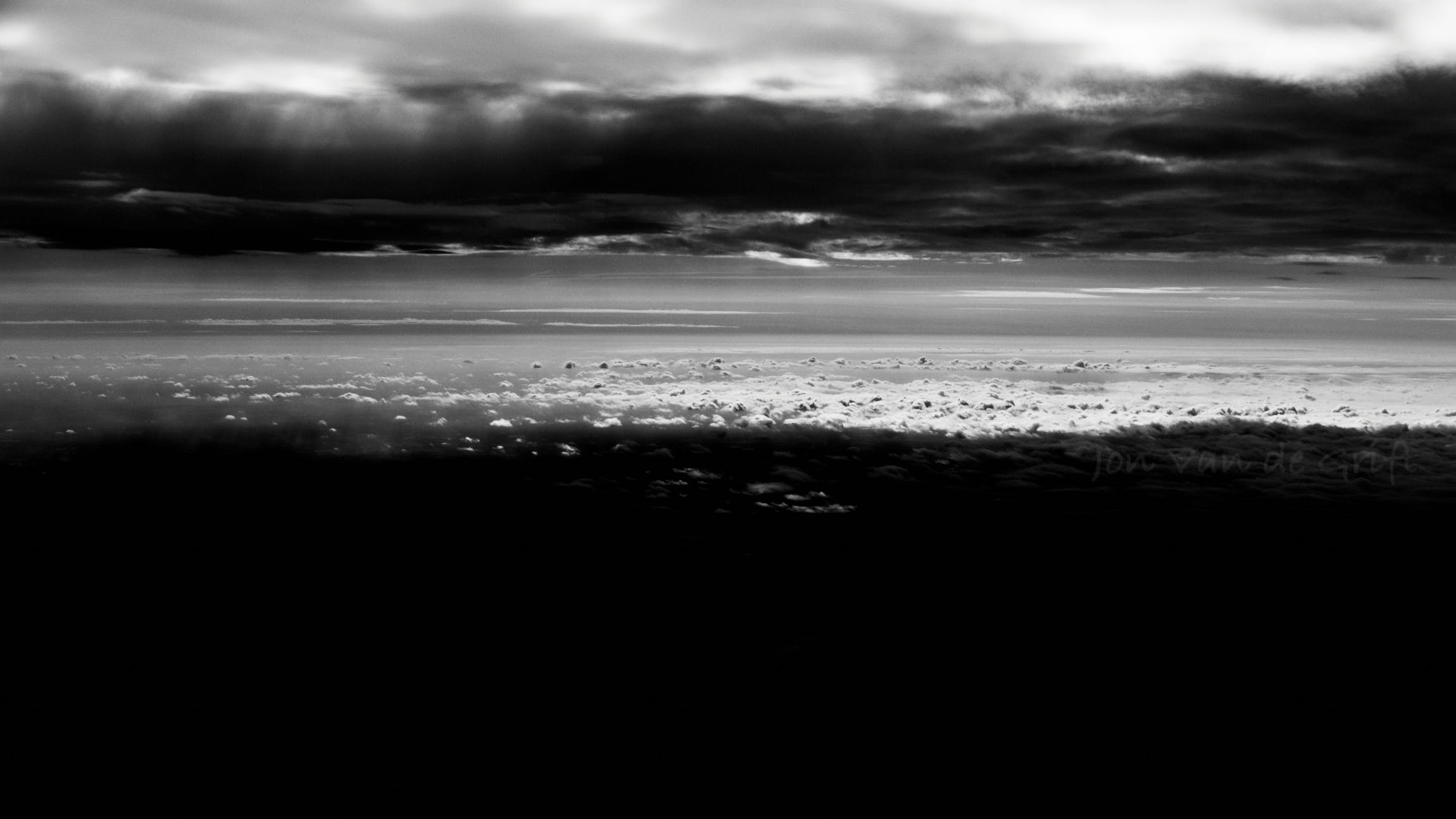 Monochrome aerial photograph of cloud layers with sun and shadow.