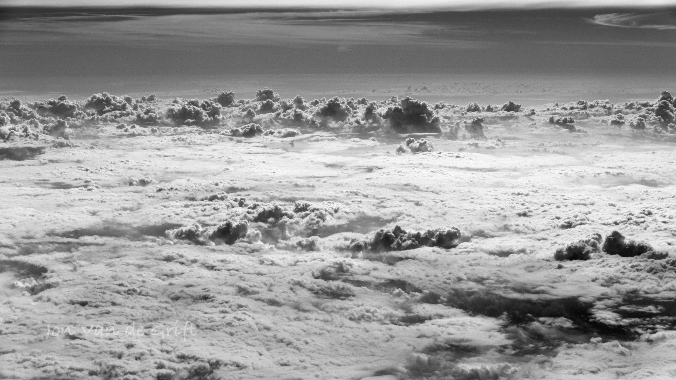 Aerial photograph of cumulus clouds captured in black and white.