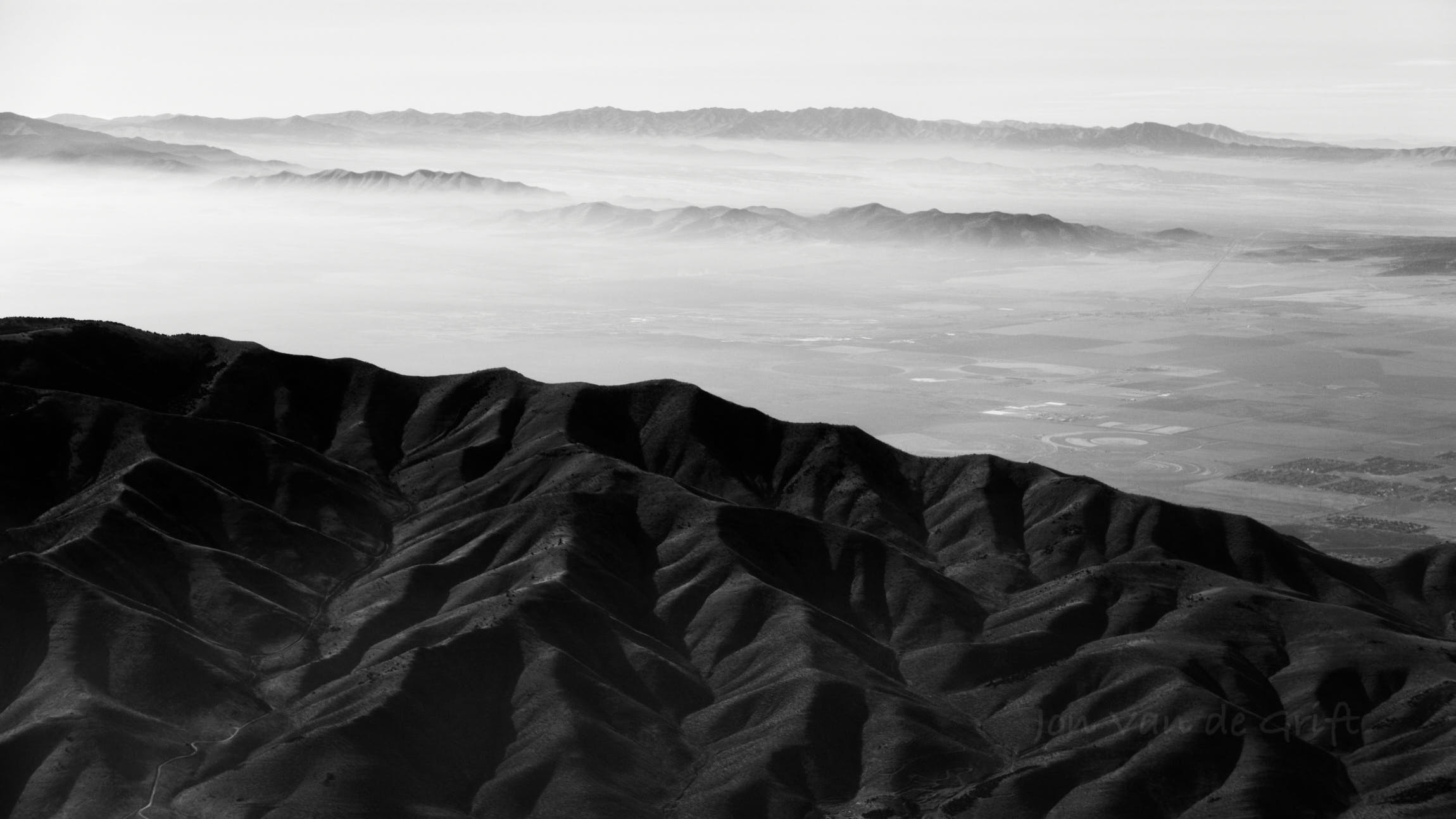 Black and white aerial photograph of dry mountains and valleys.