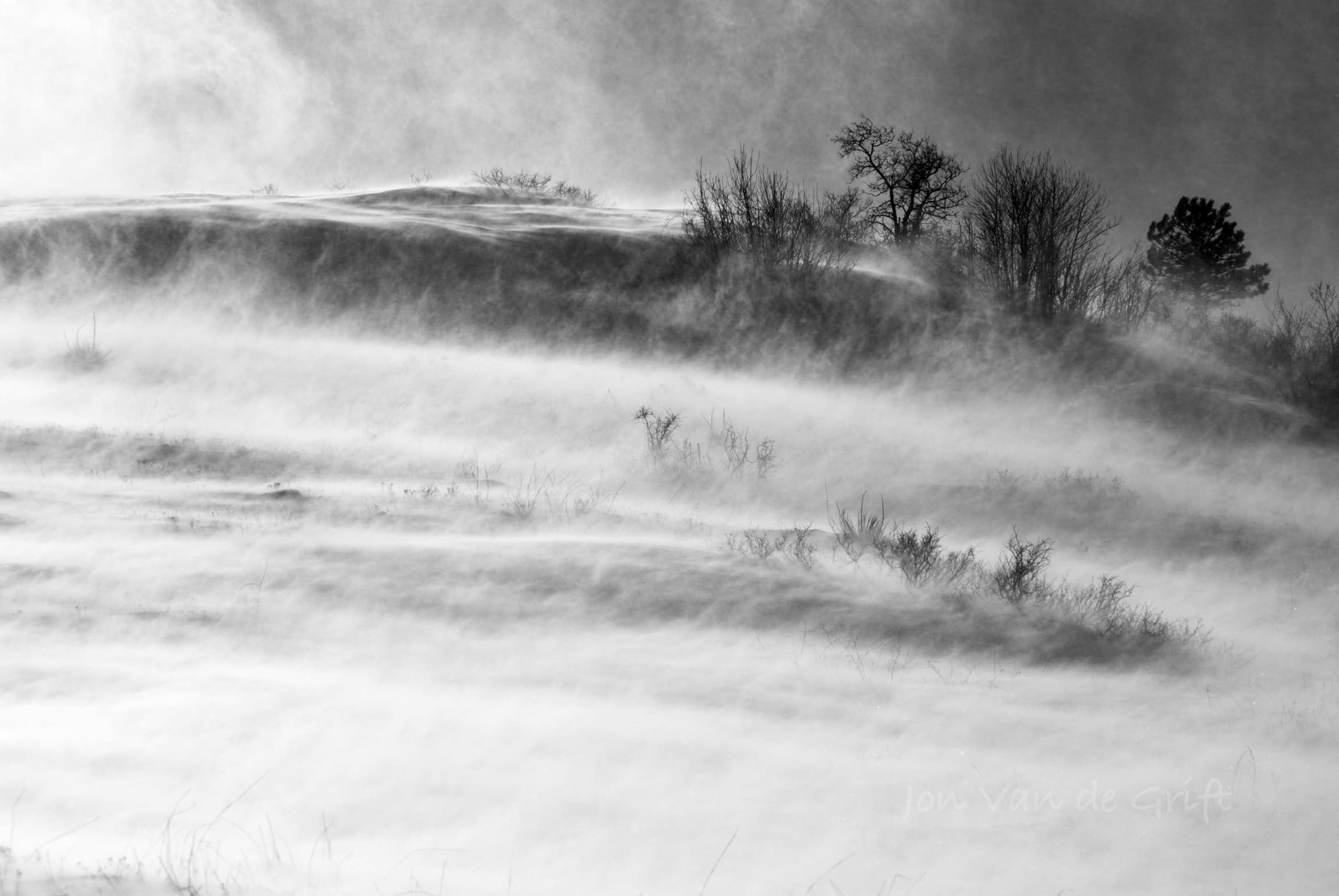 Black and white aerial photograph of a ground blizzard over a hill with sparse vegetation