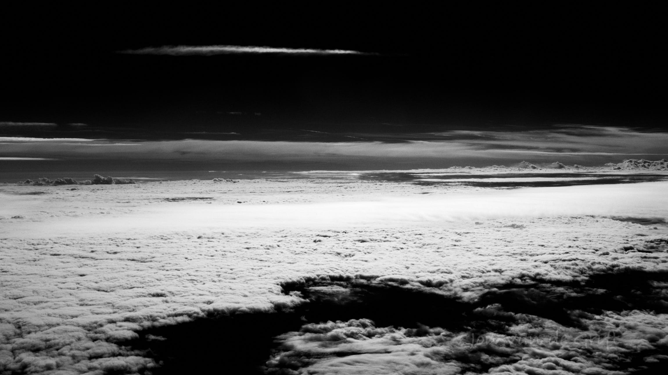 Black and white aerial photograph captured above a layer of stratus clouds.