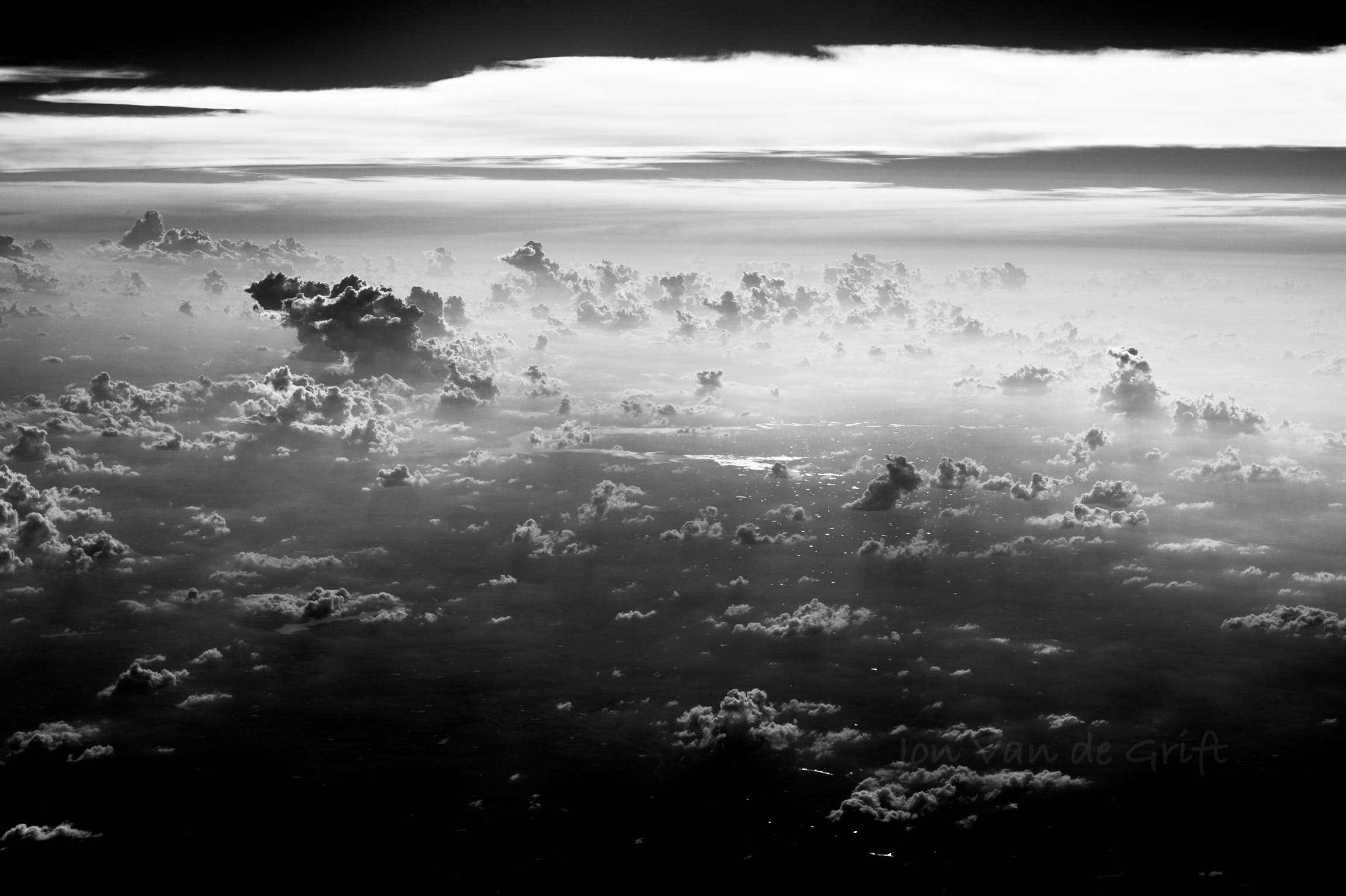 Black and white aerial photograph of distant cumulus clouds against the sun.