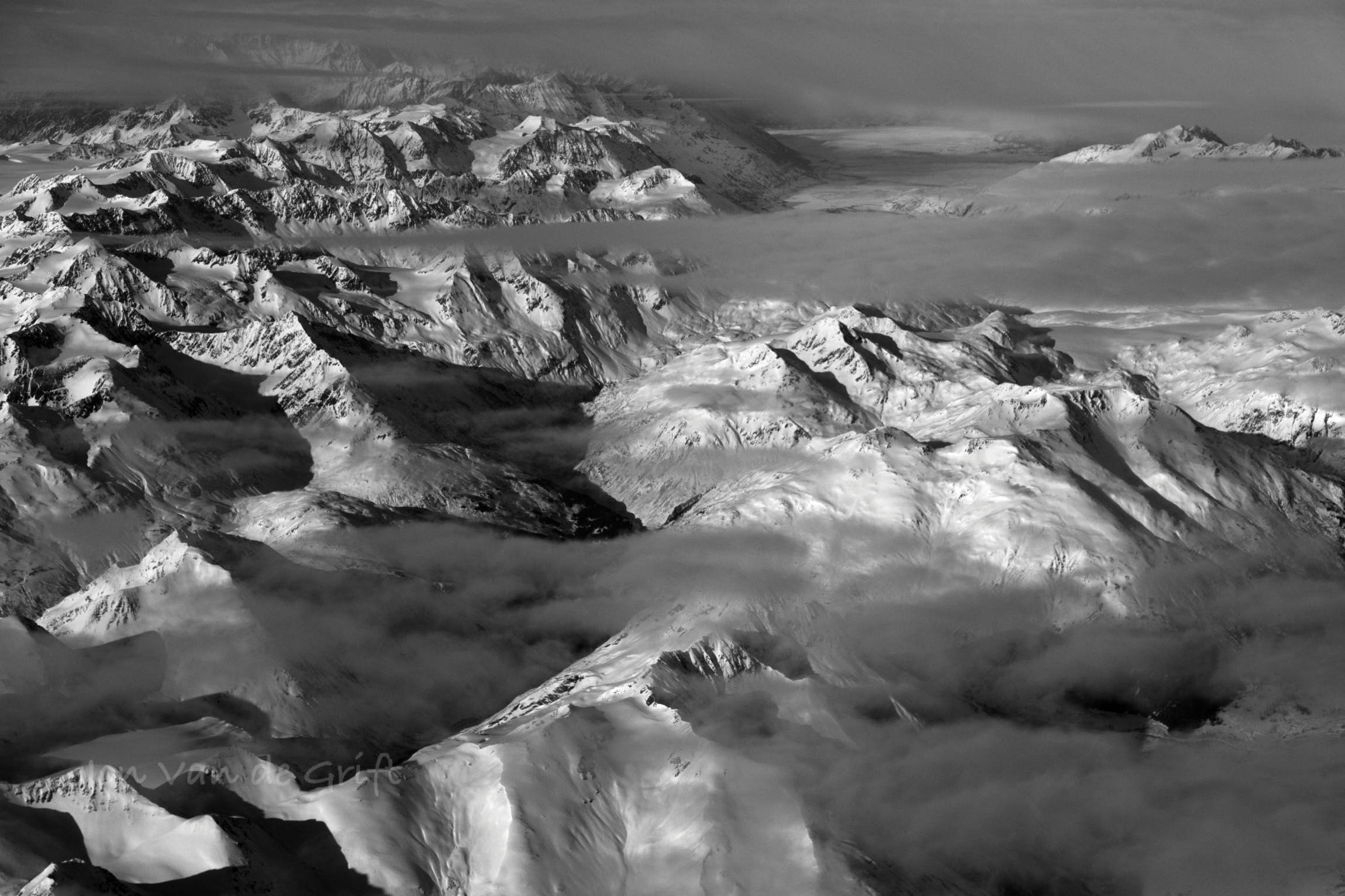 Black and white aerial photograph  of a breaking winter storm over snow covered mountains.