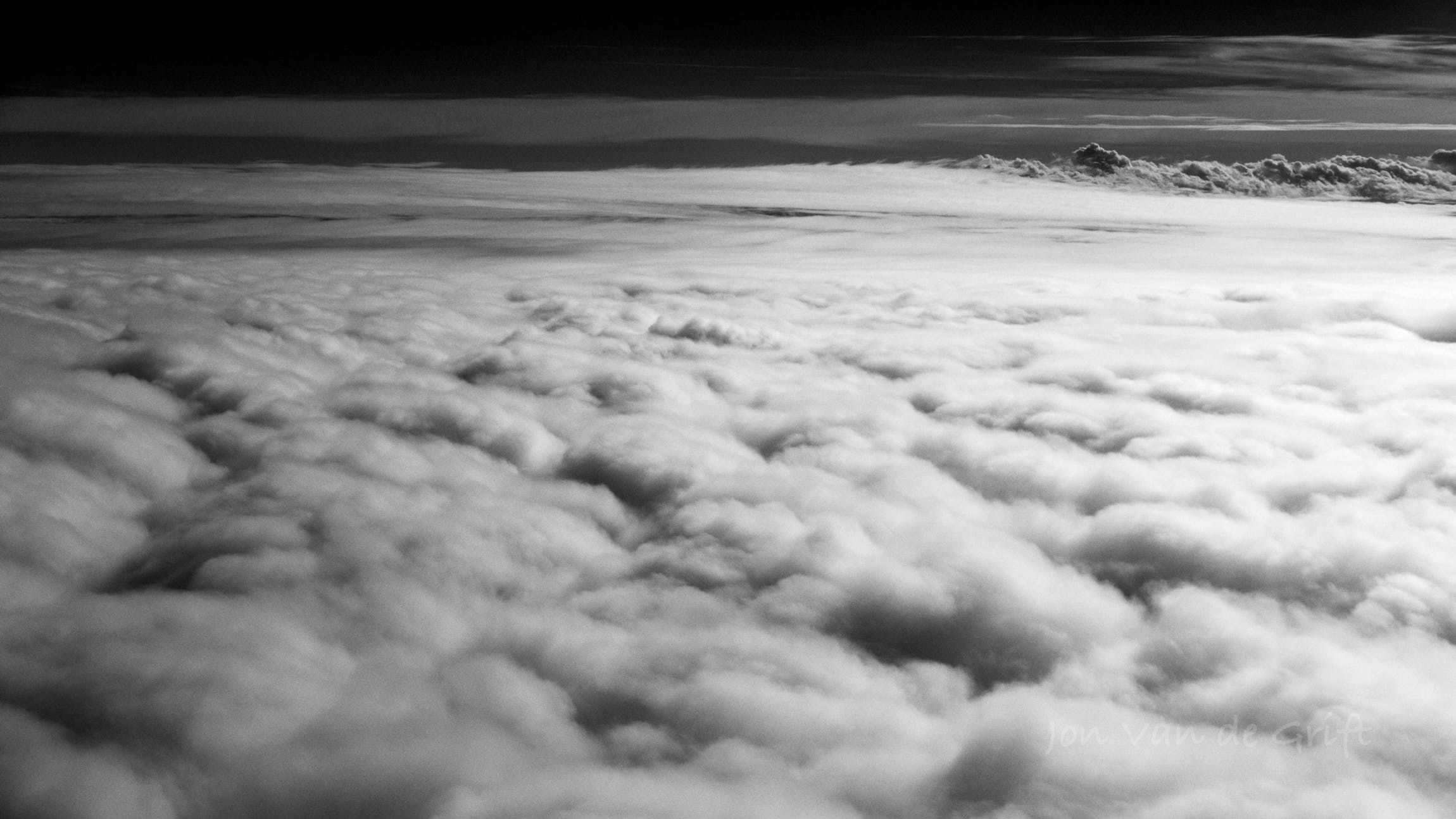 Black and white aerial photograph of cloud tops.
