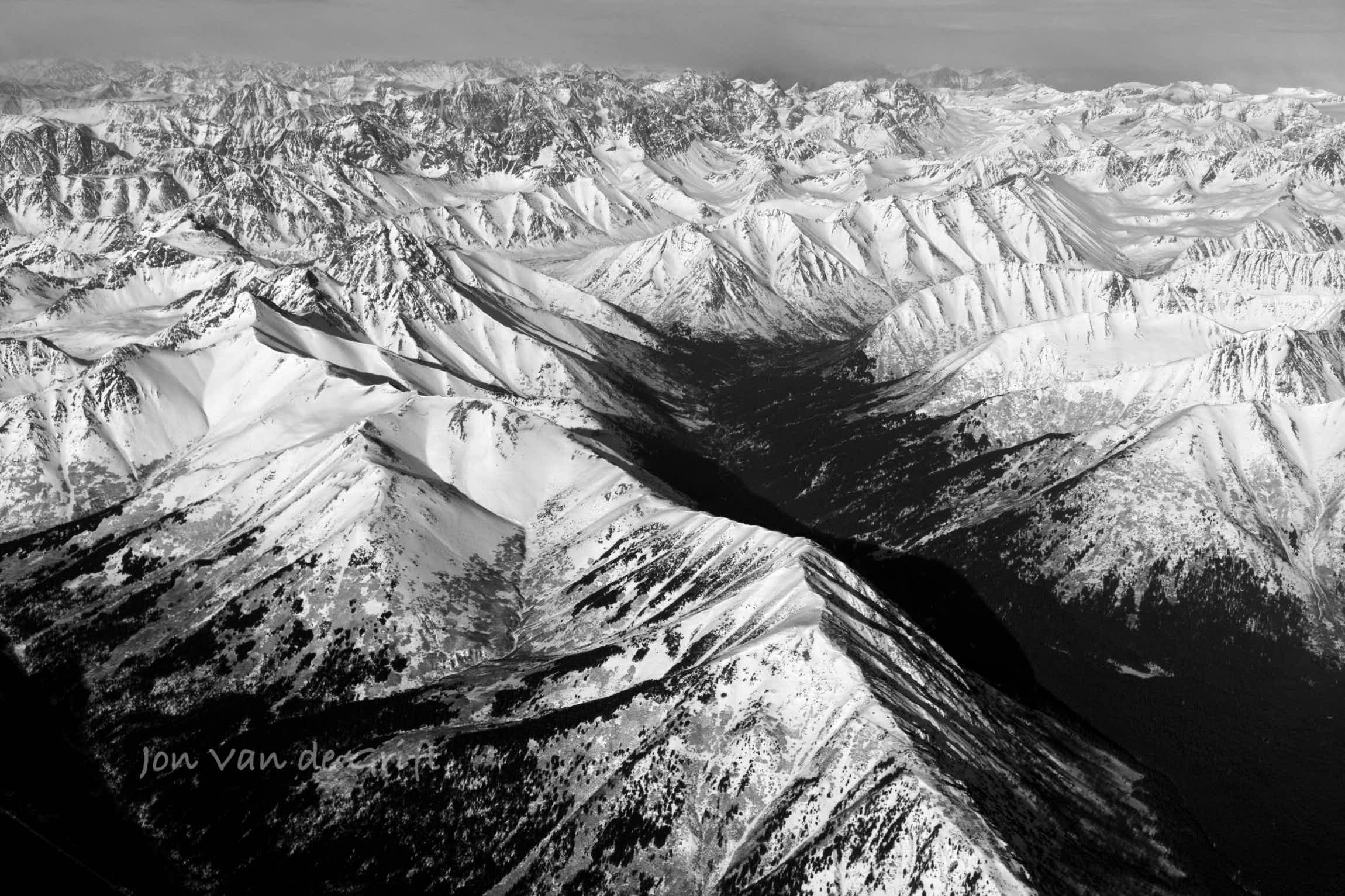 Black and white aerial photograph of snow covering mountain ranges in an Arctic winter.