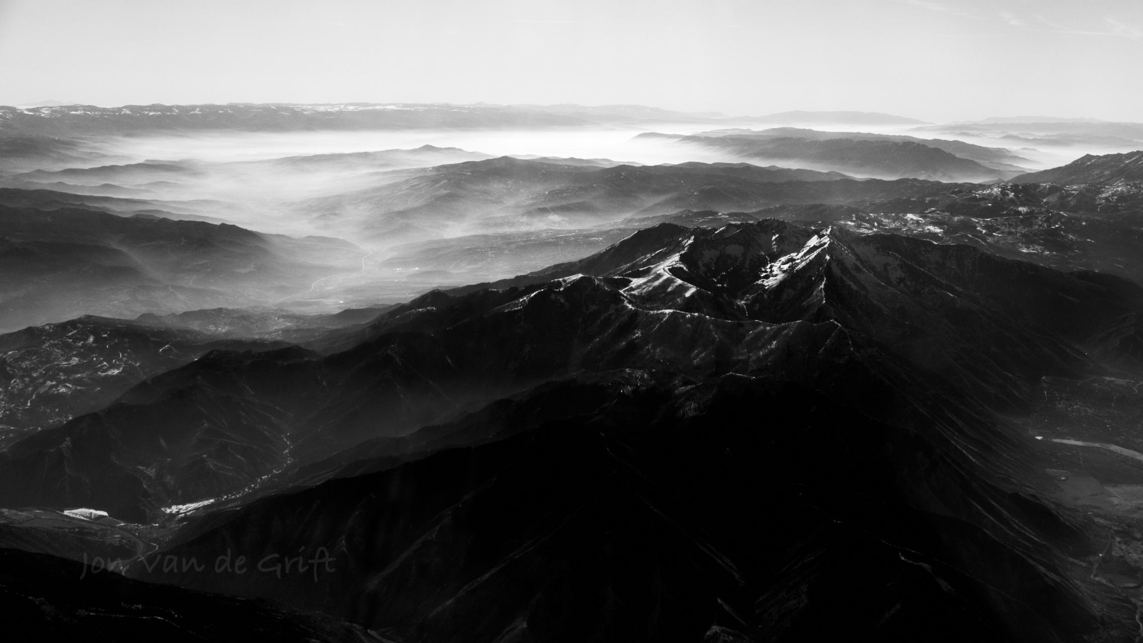 Monochromatic aerial photograph of dust and haze around a mountain summit.