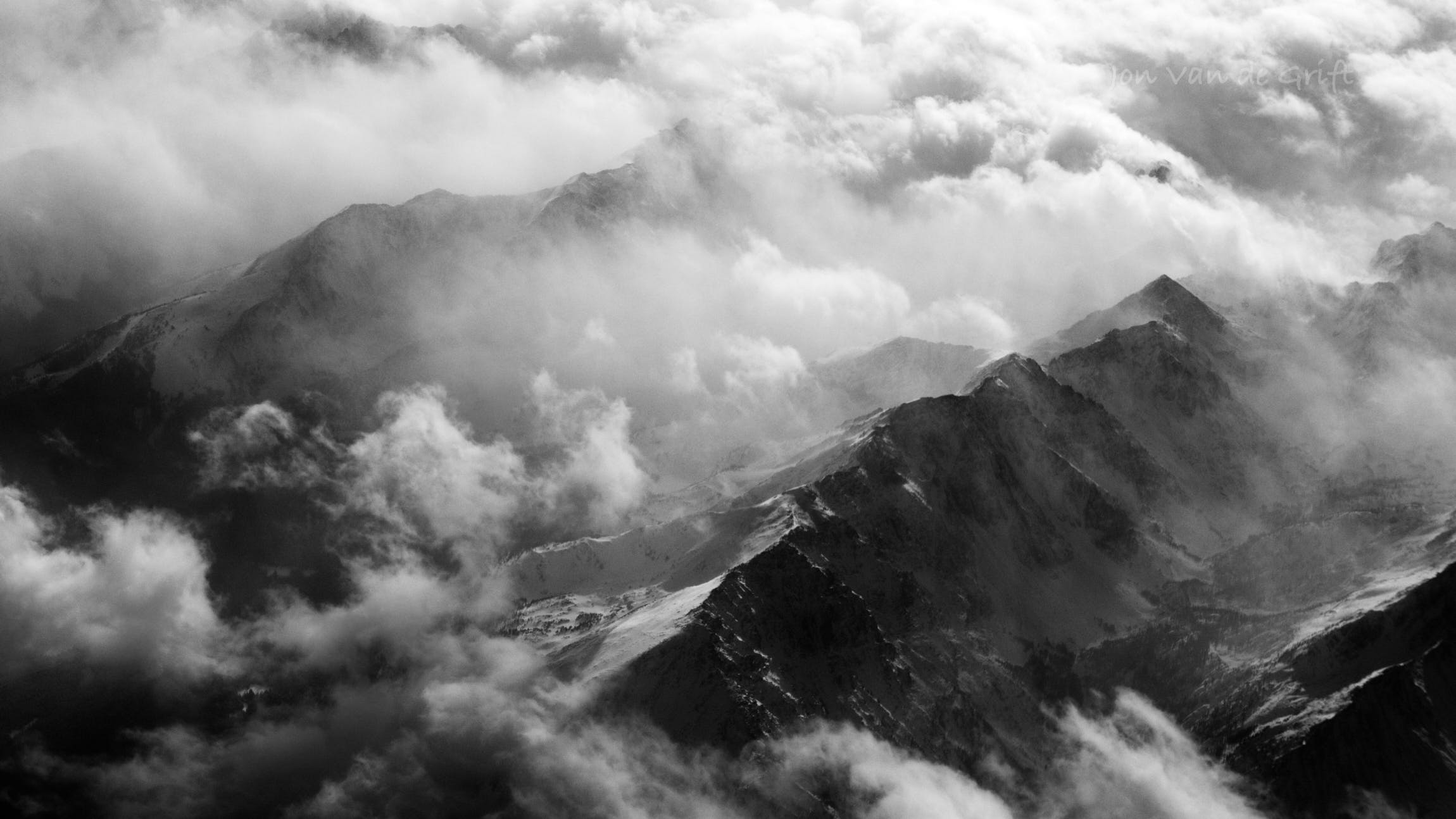 Monochrome aerial photograph of a winter storm breaking over a mountain range