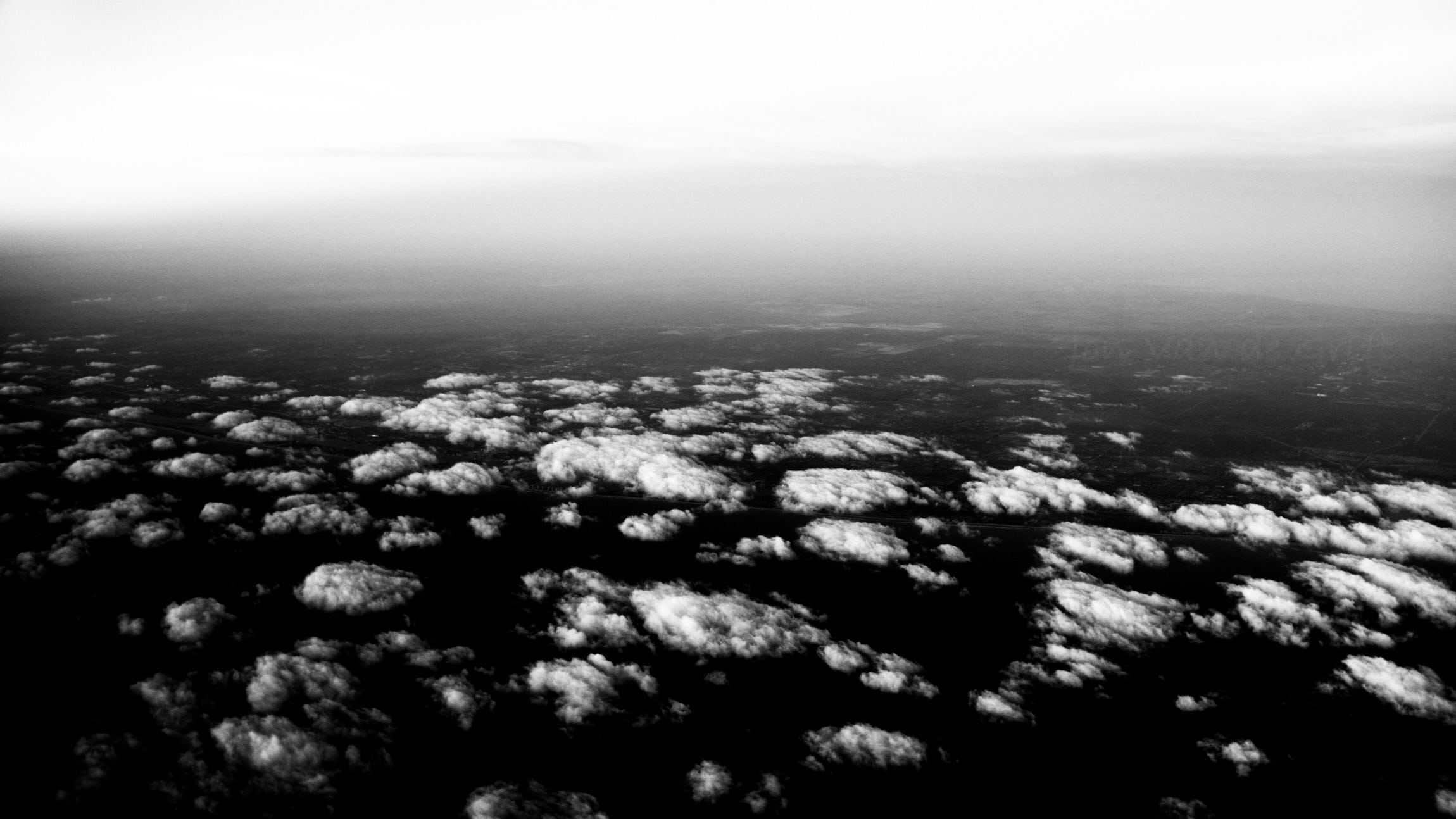 Black and white aerial photograph of clouds over land.